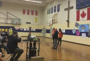 """The football players and school principal address the """"Be More Than a Bystander"""" assembly."""